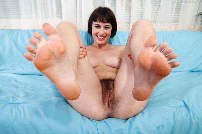 Belle brune poilue les pieds tendus