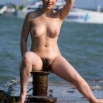 Bérénice, brune naturiste à grosse touffe, nue sur le port